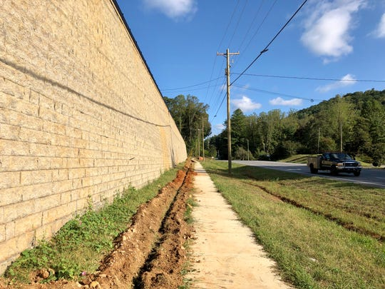 The developer of the Hawthorne at Mills Gap apartment complex says trees will be planted in the coming weeks to help soften the appearance of a large block wall.