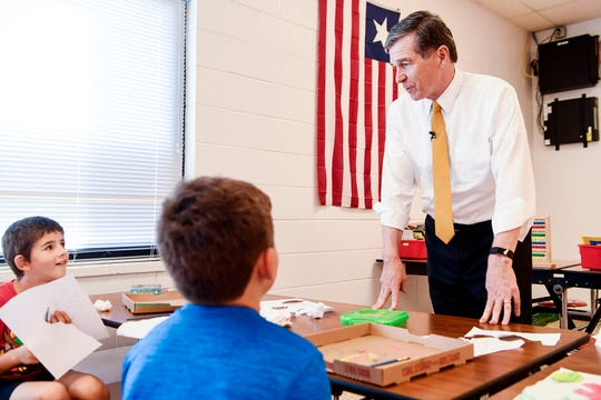 Gov. Roy Cooper talks to Merrill Rich, left, and Samuel Mace, both in third grade, as he visits North Buncombe Elementary October 10, 2019.
