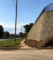 "Developer Rusty Pulliam said trees will be planted along the wall and between the sidewalk and street to help soften the appearance of the large ""castle wall"" at the new Hawthorne at Mills Gap apartments, which should open in spring of 2020."