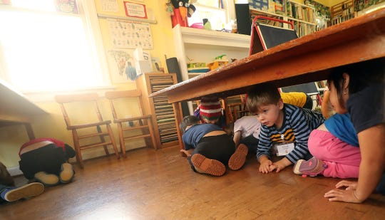 Gabriel Hollmuller, 4, takes his position under one of the tables and prepares to duck and cover during a presentation by Heather Beal at Sycamore Tree Preschool in Bremerton on Wednesday, Oct. 9, 2019.
