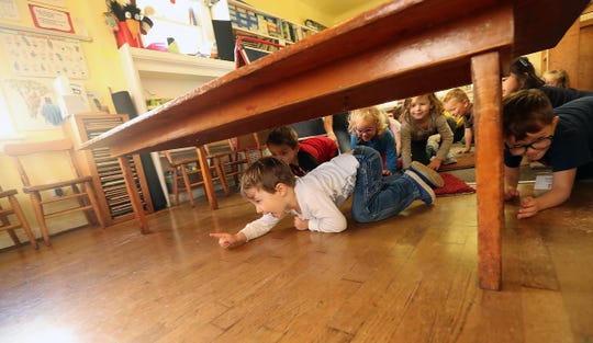 Everett Ernst, 4, leads the way as he and his fellow students crawl to take shelter underneath the sturdy tables during an earthquake drill presentation by Heather Beal at Sycamore Tree Preschool in Bremerton on Wednesday. Beal's nonprofit helps childcare centers and preschools prepare for emergencies.