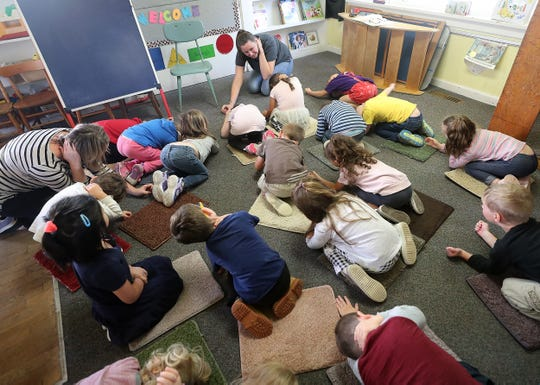 Heather Beal, back center, teaches students at Sycamore Tree Preschool the proper way to duck and cover during school on Wednesday.