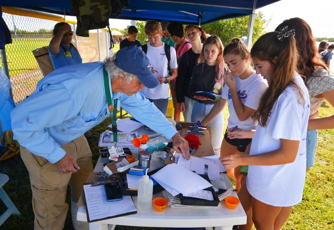 """Jim Mardulier, marine, environmental and chemistry science teacher, helps students with their data. Cocoa Beach Junior/Senior High School is one of many schools in Brevard and Indian River counties that participate annually in the """"A Day in the Life of the Lagoon"""" program, where students learn about flora and fauna, use nets to catch things near shore, catalog them and study phosphates and salinity of the river."""