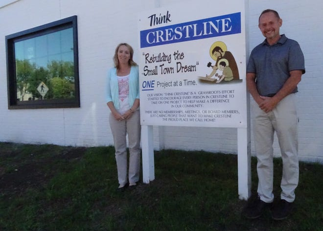 Gretchen and Joe Dzugan stand last fall beside a sign they posted in front of the building they own in downtown Crestline. It encourages all local residents to play a part in improving the community.