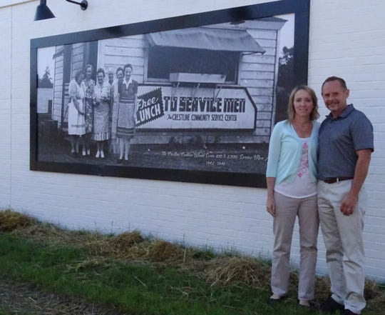 Gretchen and Joe Dzugan stand outside a building they're renovating in downtown Crestline. Historic photos have been posted along one wall of the building, embracing the community's rich heritage.