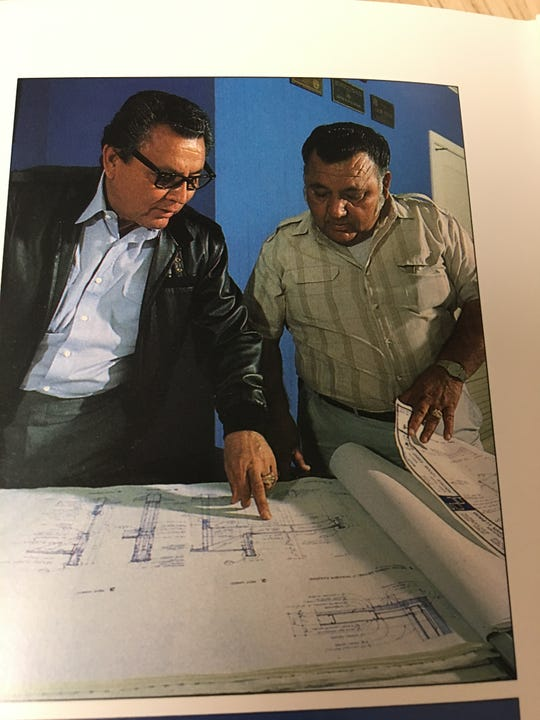 "Ismael ""I.C."" Salazar (left) goes over a blueprint."