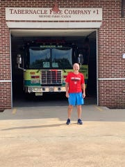 Life Center Academy headmaster Russ Hodgins stands in front of the Tabernacle Fire Company after completing a 20-mile training run recently for the Chicago Marathon. The pastor is competing in the marathon to raise money for scholarships to help underprivileged kids attend LCA.