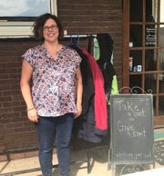 Serena DeGarmo, owner of Captivating Salon, in front of the donation coat rack on Oct. 10, 2019.
