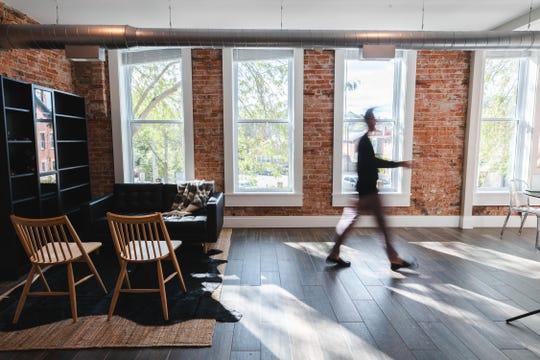Bryce Eldridge walks through the living room of his brand new luxury apartment located above Paper City Coffee.
