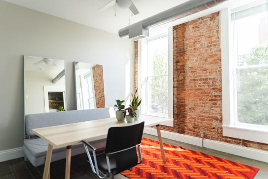 The luxury Paper City Apartments feature large windows, exposed brick and cool tones throughout the space.