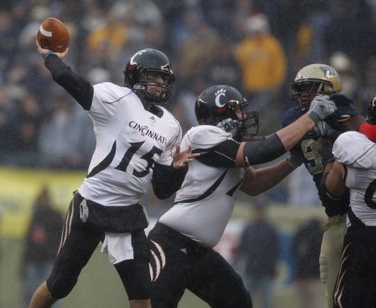 University of Cincinnati's Tony Pike, 15, throws under pressure against the  University of Pittsburgh during the second quarter of their game played at Heinz Field in Pittsburgh, Pennsylvania Saturday December 5, 2009.
