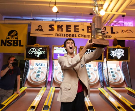 "Elan ""The Skee-Ball Kid"" Footerman, of Edison, with the championship trophy for the National Skee-Ball League Open."