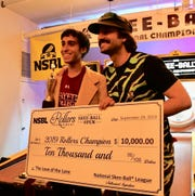 "Elan ""The Skee-Ball Kid"" Footerman, left, with former Skee-Ball world champ Joey ""The Cat"" Mucha posing with his $10,000 check after his championship win."