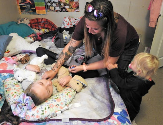 Kala Freeman with Amalia Barrick, 2, suctions suctions her daughter's airway, due to the 10-year-old's cerebral palsy. Freeman has started a GoFundMe page to help with the purchase of a handicap accessible van for transporting Danielle to school, doctor's appointments and elsewhere.