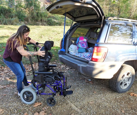 Kala Freeman takes her daughter's wheelchair out of her vehicle and sets it up. She recently established a GoFundMe page to help with funding for the purchase of a handicap accessible van which will make transporting 10-year-old Danielle Hardesty easier.