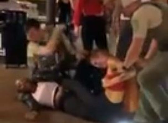 This image is a still taken from a video shot early Sept. 20 on Court Avenue in downtown Des Moines. The Iowa Department of Natural Resources conservation officers shown were investigated for their actions breaking up a fight that night between two women. One of the officers is seen in the video elbowing a woman in the head as she is being held to the ground.
