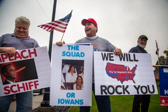 Gary Leffler, center, holds a sign supporting President Trump outside the Waukee Community Center before Rep. Rep. Cindy Axne, D-Iowa holds a town hall Thursday, Oct. 10, 2019.