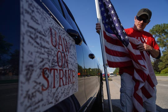 Rob Gerbig of Grand Blanc Twp. holds his American flag while talking about the signatures he has had by fellow UAW members on strike against General Motors that have signed the magnet attached to his truck while on strike outside of Flint Assembly in Flint on Wednesday, October 9, 2019. Gerbig, a third-generation veteran and General Motors worker that works as a materials handler for Flint Assembly, carries the flag while on strike due to his service.