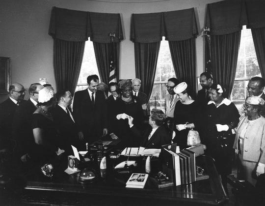 President John F. Kennedy hands pen to Rosa Gragg after designating Frederick Douglass' home as a national historic site.
