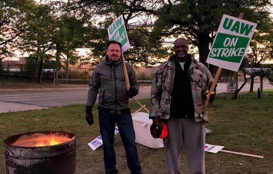 Gary Henrion, 47, and Victor Hayworth, 61, walk the early morning picket line at the body shop gate at the GM Detroit-Hamtramck Assembly Plant, Thursday Oct. 10, 2019.