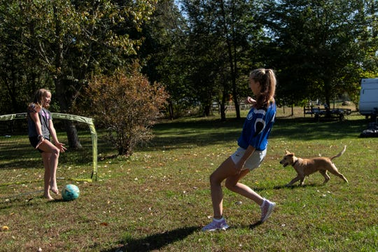 Olivia Bowen, 11, left, and her sister Brynn, 14, along with their dog Charlie, play soccer in their backyard in Marcellus, Wednesday, Oct. 9, 2019.