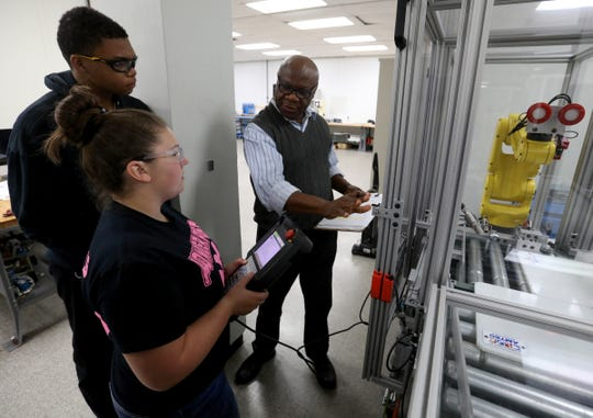 (L to R) James Kilgory, 17 and a senior at Flat Rock Community High School and Chloe Doherty, 17, a senior at Southgate Anderson High School listen to Arthur Ibegbu, a coordinator with the Downriver Career Technical Consortium Learning Center at the Ford Flat Rock Assembly, talk about the robotic arm they were controlling during class on Wednesday, October 9, 2019.