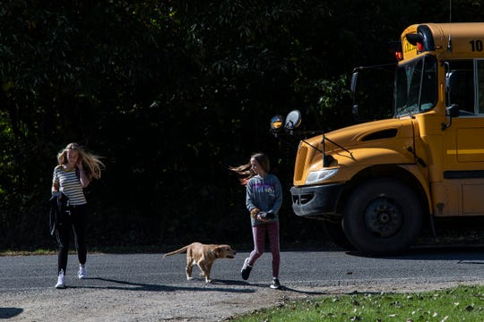 Brynn Bowen, 14, and her sister Olivia, 11, are greeted by their dog Charlie as they get off the school bus in front of their home in Marcellus, Wednesday, Oct. 9, 2019.