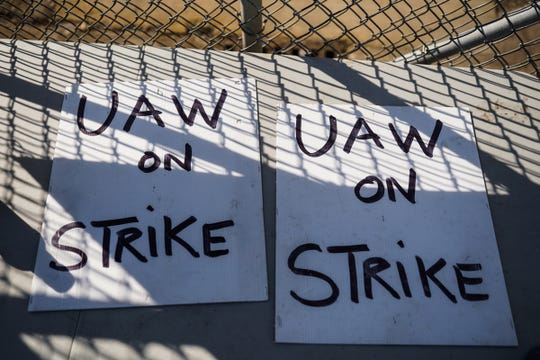 Handmade UAW strike signs lay on a table outside of General Motors Flint Assembly on Monday, October 7, 2019.