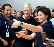Apple CEO Tim Cook, takes a photo with employees at the Steve Jobs Theater during an event to announce new products Tuesday, Sept. 10, 2019, in Cupertino, Calif.