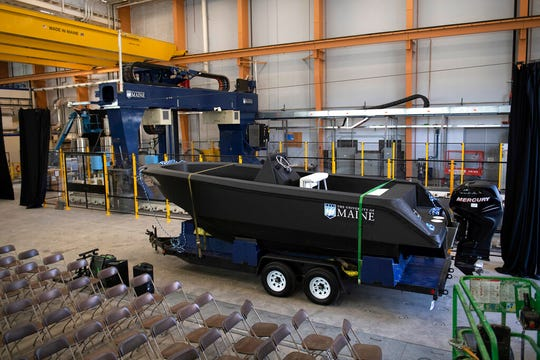 In this Wednesday, Oct. 9, 2019 photo provided by the University of Maine, a 25-foot, 5,000-pound patrol boat, center, that was produced using a large polymer 3D printer, behind left, rests on a trailer on the school's campus, in Orono, Maine. The boat was printed at the school's Composites Center on the world's largest polymer 3D printer.