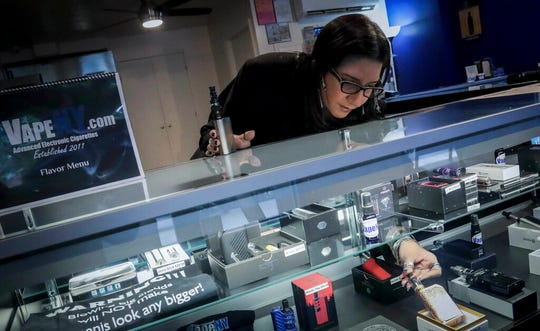 In this Tuesday, Oct. 8, 2019, photo Spike Babaian, owner of several Vape New York stores, works in her East Harlem store in New York. Sales at small businesses that sell vaping products have plunged since August, when reports of vaping-related illnesses and deaths began.