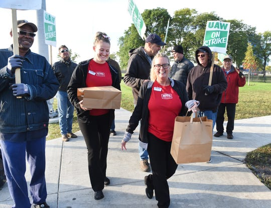 National Coney Island waitresses Megan Dadorski, left, and Julie Aluzzo deliver two dozen coney dogs and fries to striking UAW members on the picket line at the Warren Tech Center on Thursday.