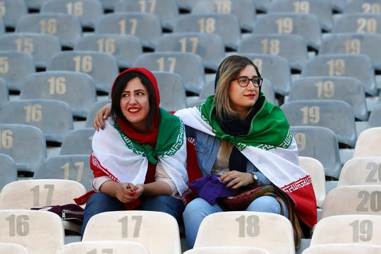 Iranian women wear their country's flag on their shoulders at the Azadi Stadium for the 2022 World Cup qualifier soccer match between Iran and Cambodia, in Tehran, Iran, Thursday, Oct. 10, 2019.