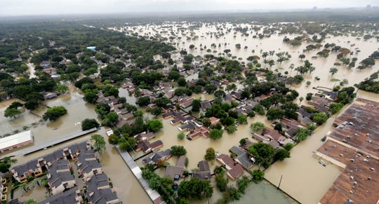 FILE - In this Aug. 29, 2017, file photo, a neighborhood near Addicks Reservoir is flooded by rain from Tropical Storm Harvey in Houston. A new study finds that FEMA buys flood-prone homes more often in wealthy, populous counties than in poor, rural areas, even though lower-income rural areas may be more likely to flood frequently.