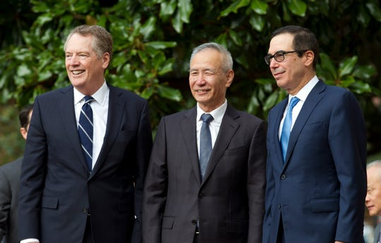 Chinese Vice Premier Liu He accompanied by U.S. Trade Representative Robert Lighthizer, left, and Treasury Secretary Steven Mnuchin, greets the media before a minister-level trade meetings at the Office of the United States Trade Representative in Washington, Thursday, Oct. 10, 2019.