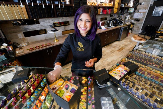 In this Monday, Sept. 16, 2019, photo Annie Rupani, owner of Cacao & Cardamom, poses for a photo inside one her shops in Houston. She's seen the amount that people spend on each visit drop in the past year.