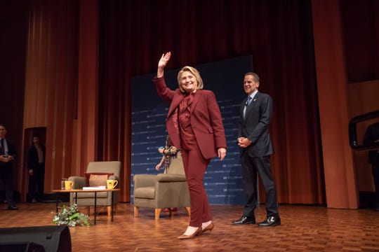 Former U.S. Secretary of State Hillary Rodham Clinton waves to the audience with Dean of Public Policy Michael Barr looking on at Rackham Auditorium on the campus of the University of Michigan.