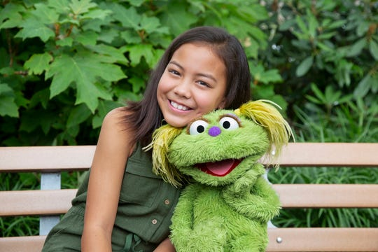 """This undated image released by Sesame Workshop shows 10-year-old Salia Woodbury, whose parents are in recovery, with """"Sesame Street"""" character Karli. Sesame Workshop is addressing the issue of addiction. Data shows 5.7 million children under 11 live in households with a parent with substance use disorder. Karli had already been introduced as a puppet in foster care earlier this year but viewers now will understand why her mother had to go away for a while."""