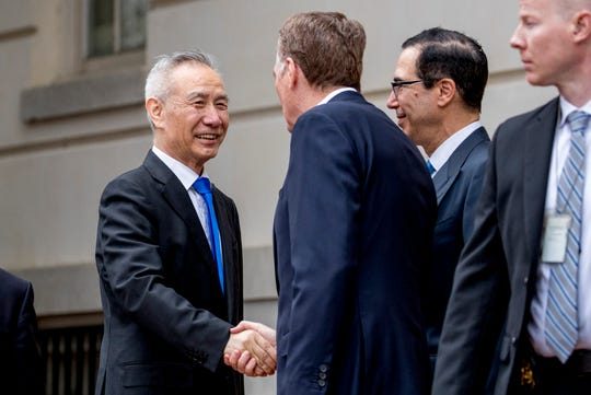 FILE - In this May 10, 2019, file photo, China's Vice Premier Liu He, left is greeted by U.S. Treasury Secretary Steve Mnuchin, second from right, and U.S. Trade Representative Robert Lighthizer, third right, as he arrives at the Office of the United States Trade Representative in Washington. China's Ministry of Commerce said Tuesday that Liu is going to Washington on Thursday for talks aimed at ending the tariff war.