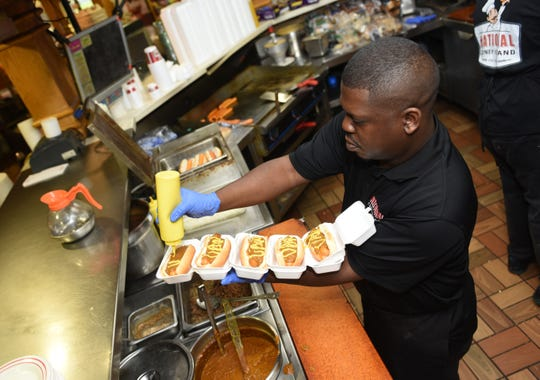 "Maurice Cunningham, manager of National Coney Island in Warren, writes ""UAW"" in mustard as he makes two dozen coney dogs to be delivered to striking UAW members at the GM Tech Center on Thursday."