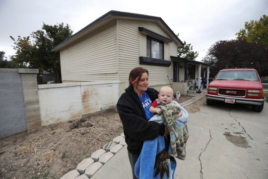 Alanna Mabey holds her grandson in front of her home, Wednesday, Oct. 9, 2019, in West Valley City, Utah. Paul Petersen sold the house this spring as complaints mounted from neighbors in the working-class area in suburban Salt Lake City, said new owner Mabey.