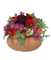 Rather than carving out the pumpkin, English Gardens' fall pumpkin floral arrangement attaches the flowers to Oasis floral foam on a saucer.