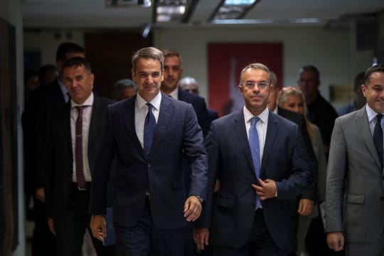 Greece's Prime Minister Kyriakos Mitsotakis center left, and Greek Finance Minister Christos Staikouras, center right, arrive at a meeting in Athens, on Wednesday, Sept. 11, 2019. Mitsotakis chaired Wednesday a meeting of cabinet ministers on economic policy.