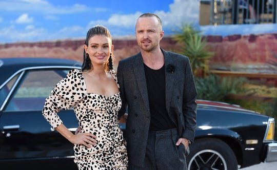 """Cast member Aaron Paul, right, and Lauren Parsekian arrive at the Los Angeles premiere of """"El Camino: A Breaking Bad Movie,"""" at the Regency Village Theatre, Monday, Oct. 7, 2019, in Westwood, Calif."""