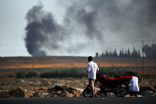 People in Akcakale, Sanliurfa province, southeastern Turkey, at the border with Syria, watch smoke billowing from targets inside Syria, during bombardment by Turkish forces, Thursday, Oct. 10, 2019.