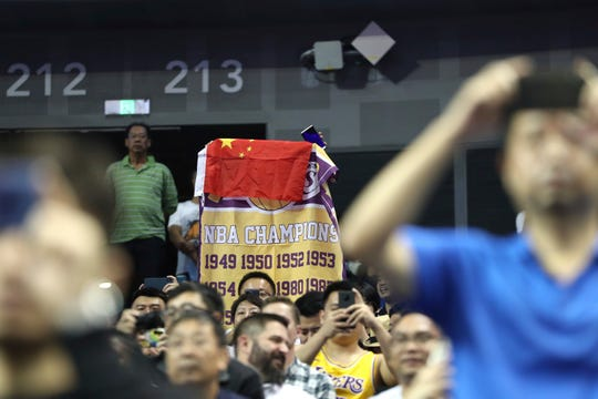A fan drapes a Chinese national flag over a Lakers banner during a preseason game between the Nets and Lakers at the Mercedes Benz Arena in Shanghai, China on Thursday.