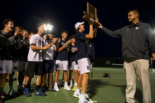 Reitz's William Hays, front center, receives the IHSAA regional title trophy from Tom Bealmear, right, as his teammates and Coach Cole Claybourn celebrate behind him at Evansville's North High School, Wednesday evening, Oct. 9, 2019. Reitz won 3-2 over Castle to gain its first regional title in school history.