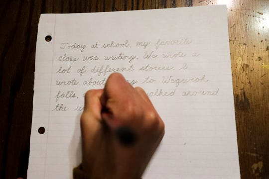 Claire Nesvacil, 12, writes about her day at school on Oct. 9, 2019, at their home in Green Bay.