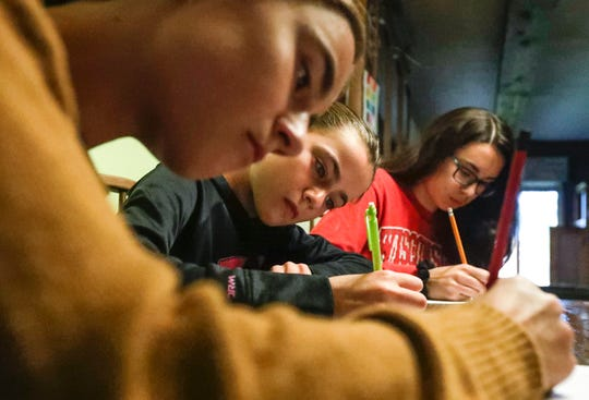 Claire, 12, Evelyn, 10, and Grace Nesvacil, 14, write about their day at school on Wednesday, Oct. 9, 2019, at their home in Green Bay, Wis. The Nesvacil family has won awards at the state and national levels for their penmanship. Claire, left, was the state winner for handwriting in fourth and fifth grade. Evelyn, middle, was the state winner and national semifinalist in third grade. Grace, right, was the national winner in fifth grade and went to state in third and fourth grade.