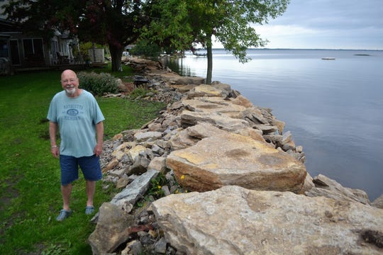 Tom Fulton stands next to the rip rap protecting his home from the water of Green Bay. This summer, Fulton bolstered 300 feet of  rip rap from the 1970s with additional stone.